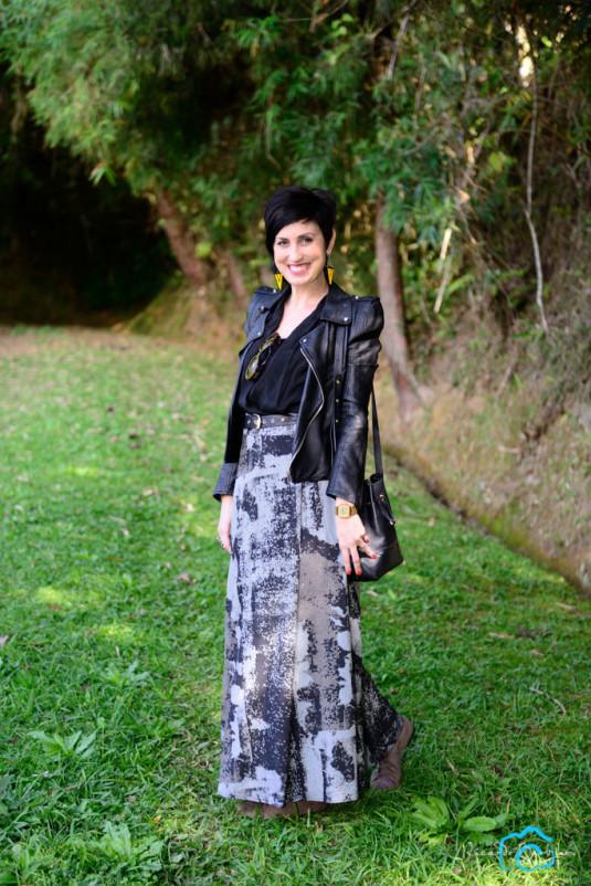 jaqueta com ombreiras de couro preta, saia longa com estampa em pixels preta, cinza e branca, bota cinza, macaquinho preto usado como blusa e com renda atrás, brincos amarelos