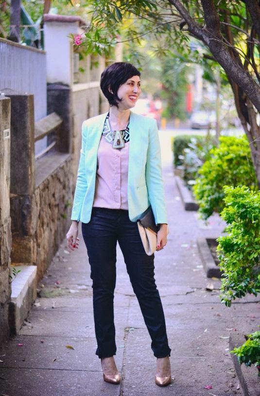 camisa rosa claro, blazer menta, calça preta, scarpin dourado e colar gigantesco de acrílico nas cores preto, rosa e menta