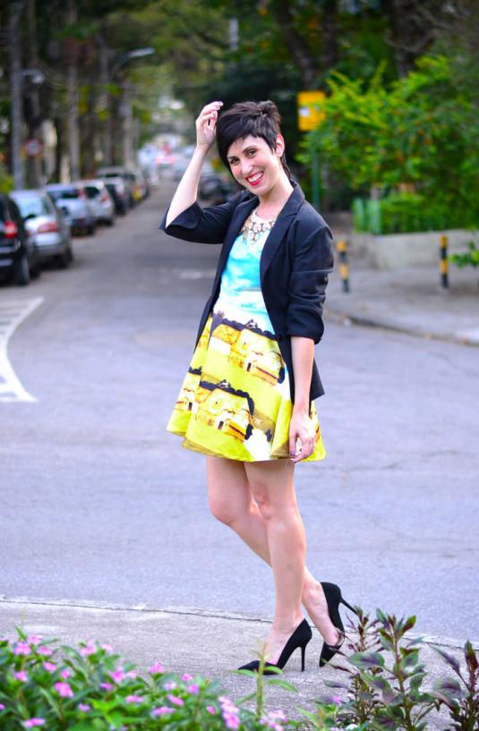 vestido rodado com estampa barroca em azul e amarelo, blazer preto, scarpin preto e colar dourado de triângulos