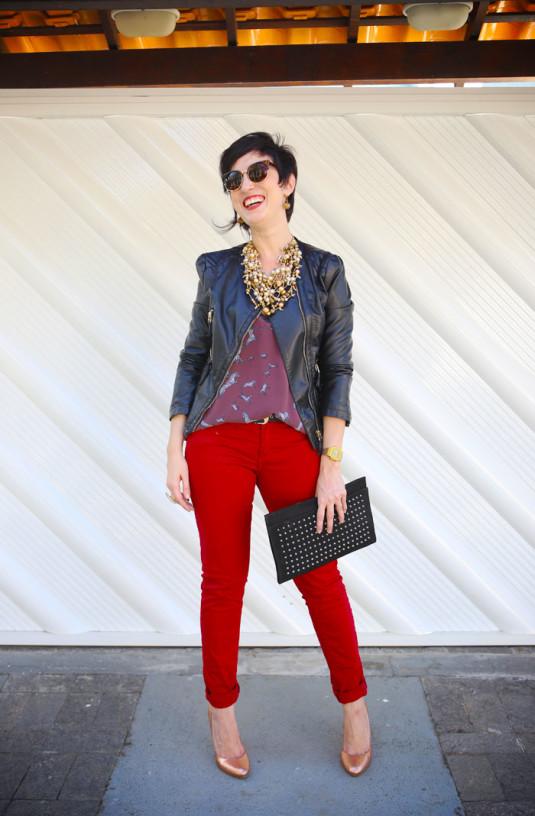 calça vermelha justa, scarpin dourado, blusa de alça vinho com estampa de zebras, maxi colar de bolinhas douradas, jaqueta de couro fake preta
