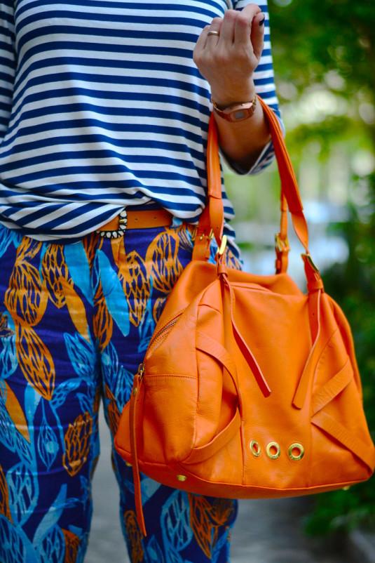 calça estampa azul e laranja de linho, blusa de manga três quartos de listras azuis, sapatilha cinza e bolsa laranja