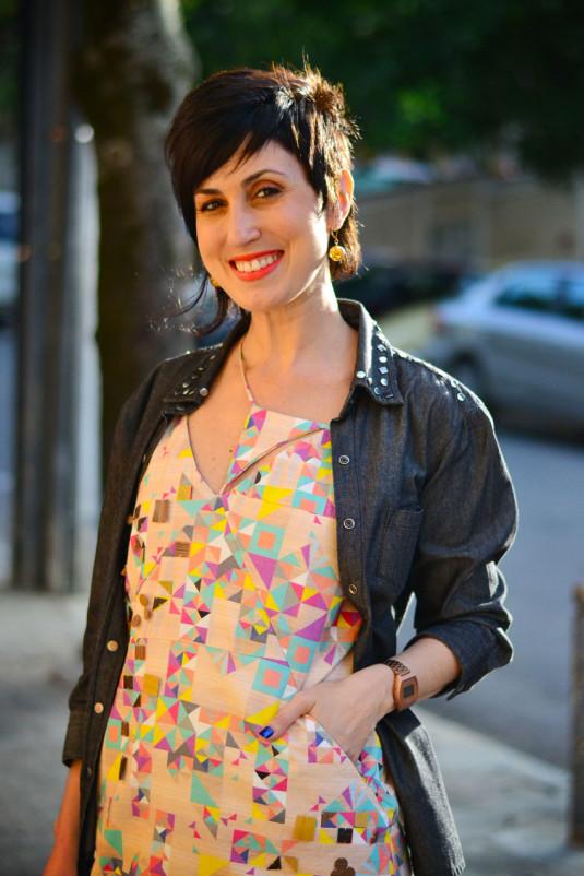 vestido curto assimétrico com estampas de triângulos rosas, amarelos, azuis, verde-água e fundo pêssego, oxford rosa claro, bolsa laranja e camisa jeans black