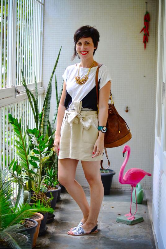 camiseta branca com triangulos pretos, saia de linho cru, sandália rasteira com estampa de folhagens pb, bolsa saco marrom tressê