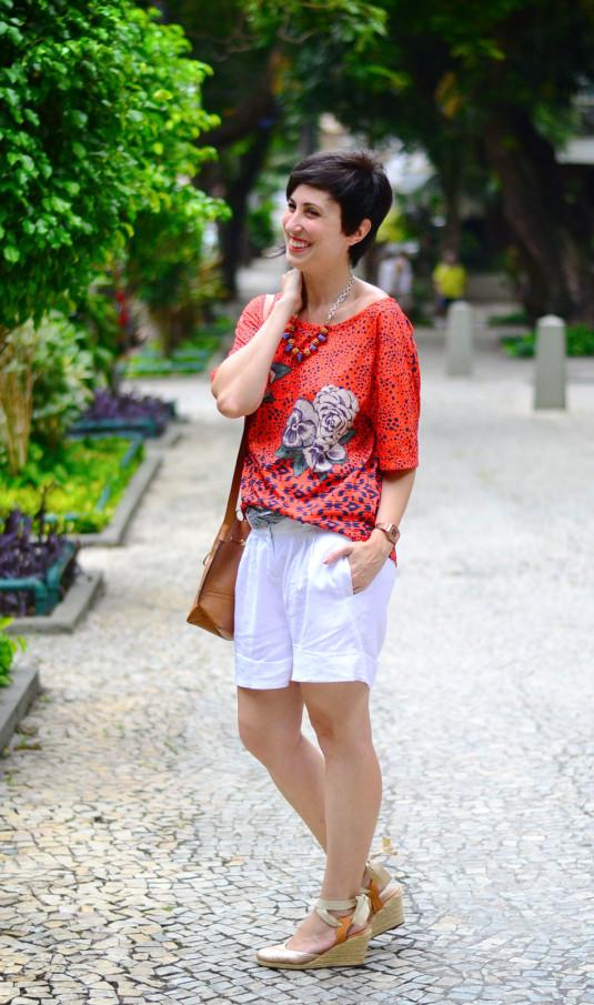 blusa laranja com pintas azuis e rosas brancos e folhas verdes, colar azul, vermelho e dourado, bermuda de linho branca com lenço cinza, espadrilhe dourada e bolsa saco caramelo
