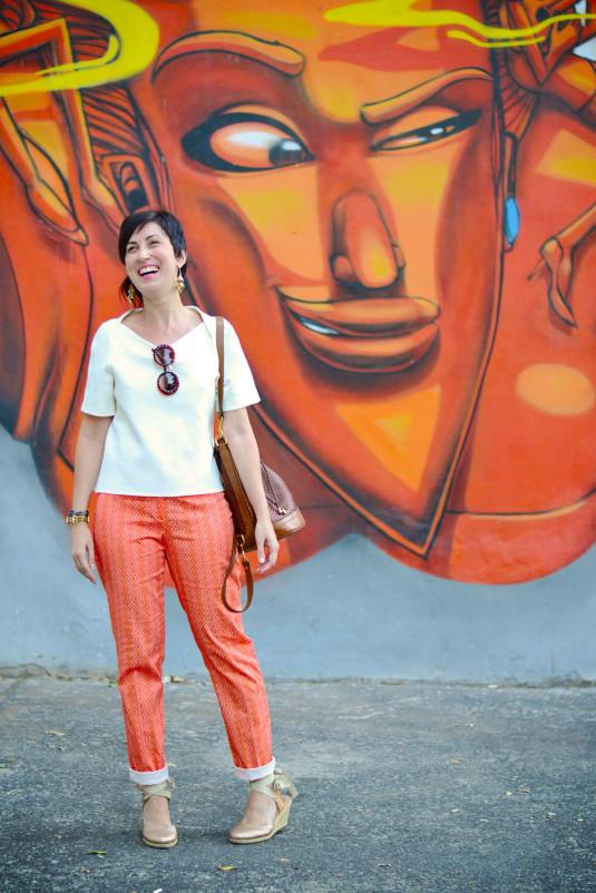 calça reta de estampas pequenas triangulares na cor laranja, espadrilhe de salto dourada, blusa branca estruturada, bolsa saco marrom tressê