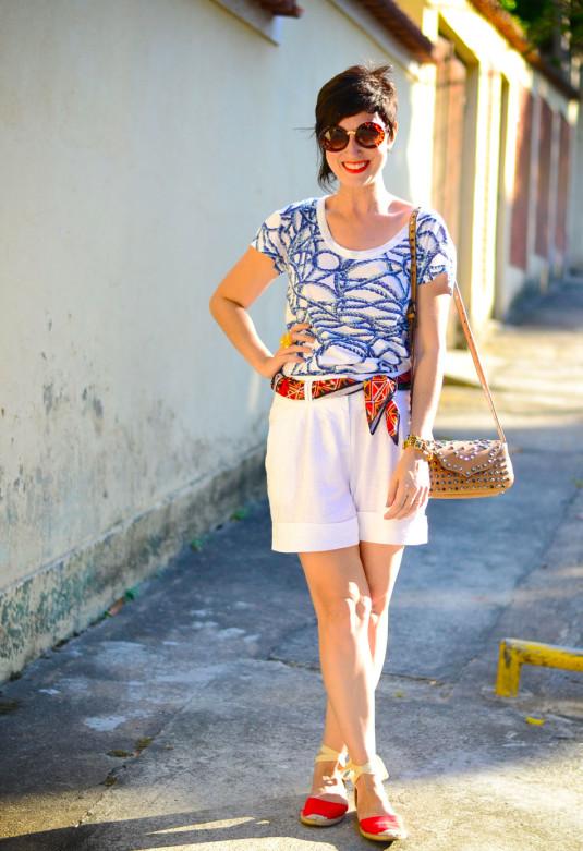blusa de estampa de cordas de navio azuis, bermuda branca de linho, espadrilhe vermelha rasteira, lenço vermelho na bermuda como cinto e bolsa pequena de tachas caramelo