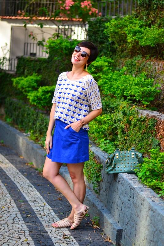 blusa de manga de linha branca com triângulos azuis de dourados, saia azul trapézio, sandália de tiras nude, bolsa verde de tachas
