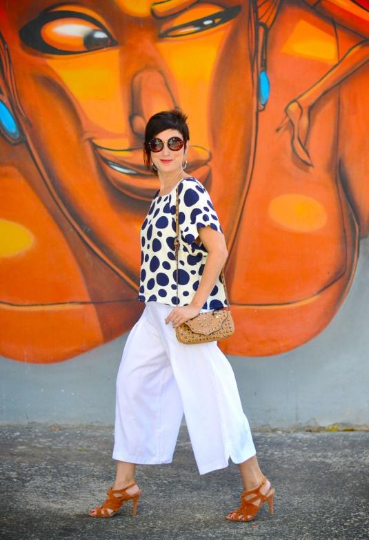 pantalona ampla branca curta, sandália de tiras trançadas caramelo, blusa soltinha de mangas curtas branca com estampas de bolas azul escuras e bolsa pequena de tachas caramelo clara