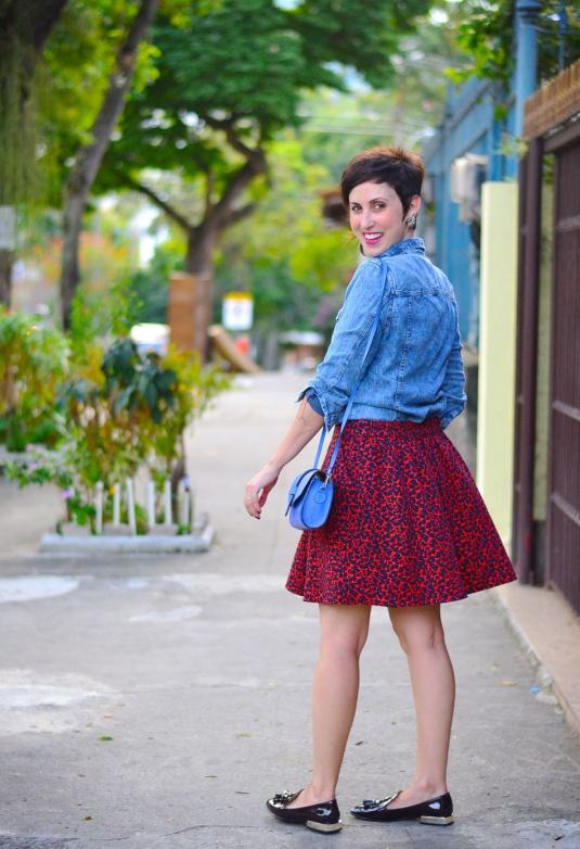 saia estampa oncinha vermelha com azul, mocassim com tessels envernizado marrom meio vinho, camisa jeans, bolsa pequena azul tiracolo
